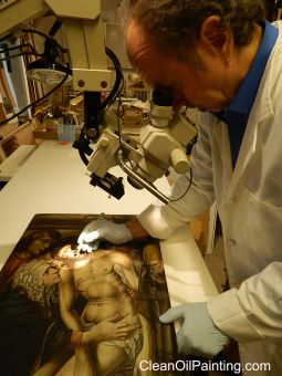 Art conservator Bruce Wood using a microscope to repair a centuries-old oil painting